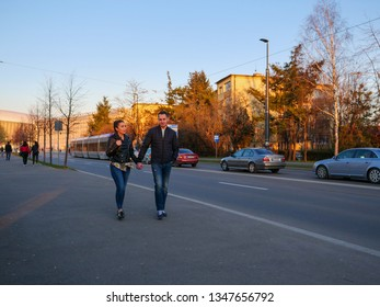 Young couple walking on the sidewalk in the evening at sunset in Cluj-Napoca, Romania, March 23, 2019