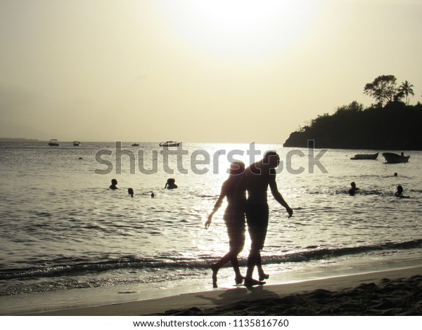 Young couple walking on the tropical beach at sunset