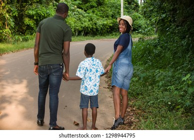 young couple walking in a park with their child smiling.