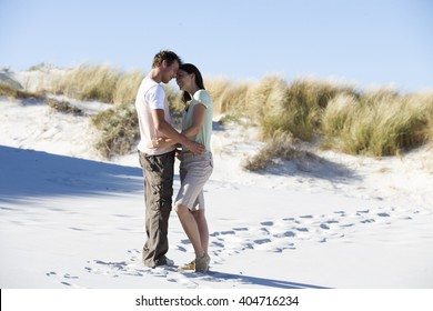 A young couple walking in sand dunes