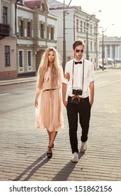 Young couple walking up the street. Retro vintage fashion portrait in summer