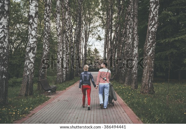 Young couple walking with a stroller on a birch alley in the park