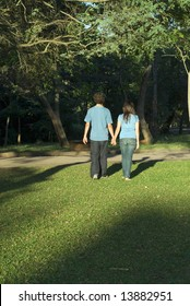 Young couple walking through a park holding hands on a sunny day. They are facing away and you can see their shadows. Vertically framed photograph