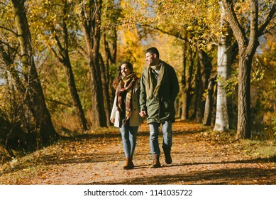 Young couple walking together outdoor in autumn. Two lovers enjoying fall season leisure in nature.