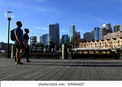 Young couple walks along Sydney Circular Quay wharf in Sydney Cove near The Rocks in Sydney New South Wales, Australia