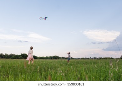 A young couple walks on the field near the forest. Couple flying a kite.
