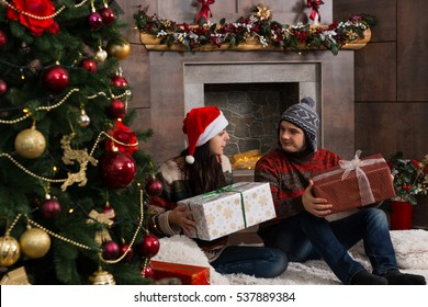 Young couple in warm sweaters and funny winter hats rejoice at their presents while sitting sitting on a rug in front Christmas tree