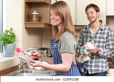 Young Couple Washing Up At Sink Together
