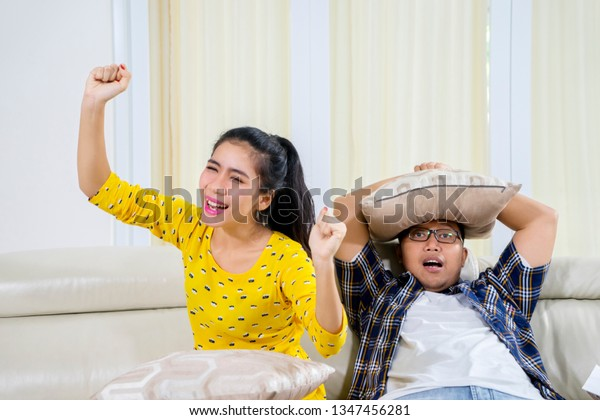 Young couple watching basketball match on tv with different emotions of win and lose