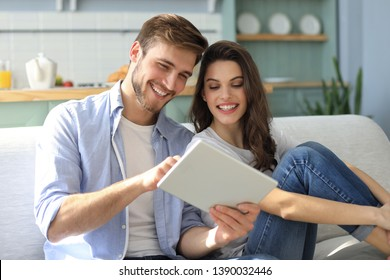 Young couple watching media content online in a tablet sitting on a sofa in the living room.