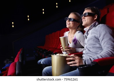 Young couple watching a movie in 3D glasses in cinema