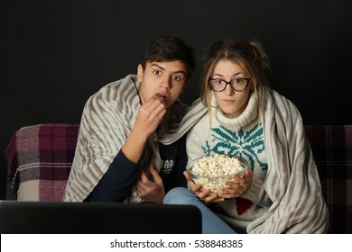 Young couple watching a movie in the evening on the sofa.