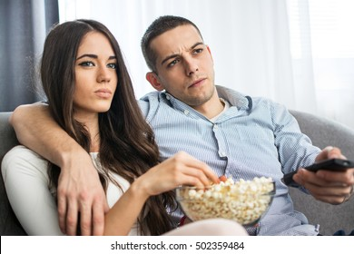 Young couple watching a movie at home.