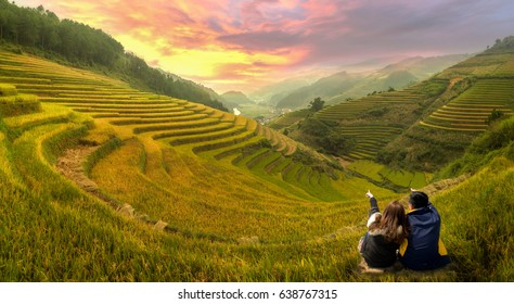 Young couple watching the scenery rice terraces at sunset in Mu cang chai,Yenbai,Vietnam.