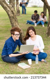 Young couple watching something on the laptop while resting on campus