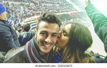 Young couple watching sport soccer match in football stadium with blurred supporters around - Happy people having fun together on weekend sporty event - Love and game concept - Focus on man face