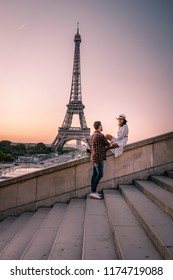 young couple watching Sunrise by the eifel tower Paris France, man and woman looking eifel tower during sunrise