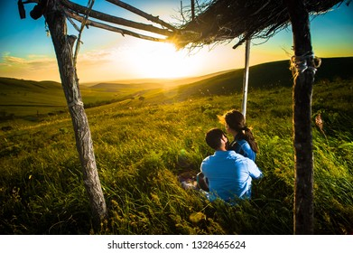 young couple watching at sunset while sitting under the hovel