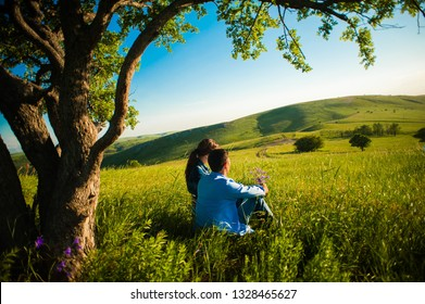 young couple watching sunset while sitting under old tree