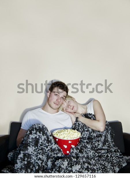Young couple watching television and eating a huge bowl of fresh buttered popcorn comfortably wrapped in a blanket.