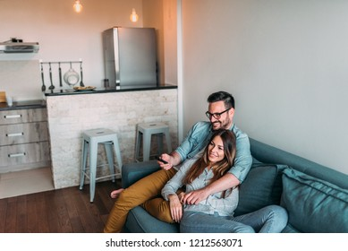 Young couple watching television at home.