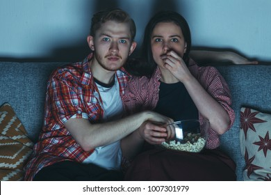 young couple watching thriller movie in dark room with popcorn on sofa fully attention