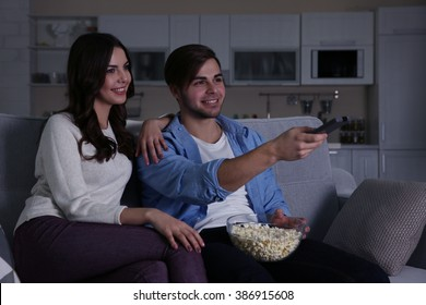 Young couple watching TV  in the evening on a sofa at home