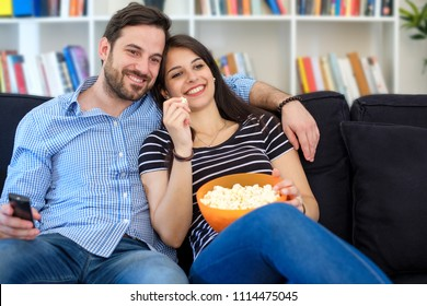 Young couple watching tv at home and having fun