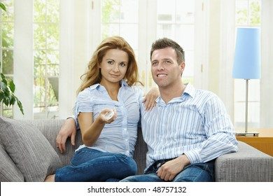 Young couple watching TV at home, sitting on couch, holding remote control in hand.
