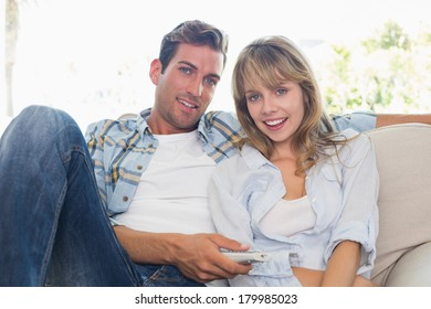 Young couple watching tv on sofa in the living room at home