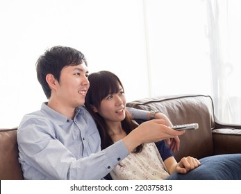 Young couple watching TV in the sofa of the living room