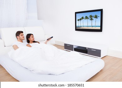 Young couple watching TV while lying in bed at home