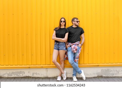 Young couple wearing black t-shirts near color wall on street