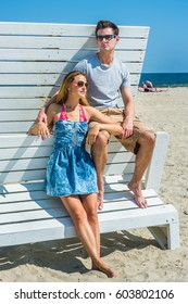 Young couple wearing glasses, barefoot, dressing in summer beach outfits, relying on each other on wooden structure at Sandy Hook Beach, New Jersey,  under sun, looking around.