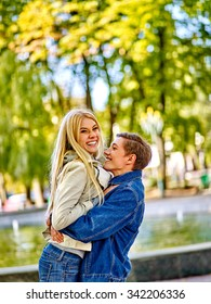 Young couple wearing jeans hugging and flirting in  park  and looking away.