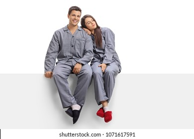 Young couple wearing pajamas sitting on a panel isolated on white background