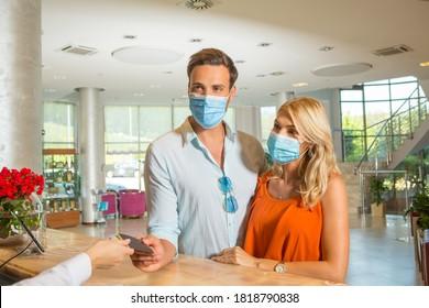 Joven pareja con protección de mascarillas en la recepción del hotel