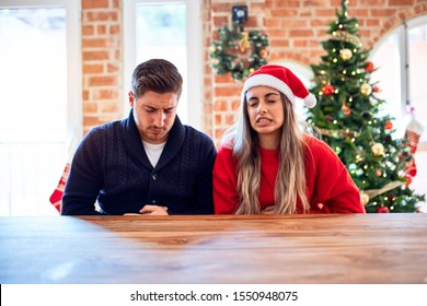 Young couple wearing santa claus hat sitting on chair and table around christmas tree at home with hand on stomach because nausea, painful disease feeling unwell. Ache concept.