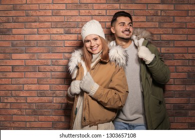 Young couple wearing warm clothes against brick wall, space for text. Ready for winter vacation