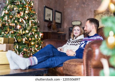 Young couple wearing warm socks and jerseys while sitting on the sofa near decorated Christmas tree