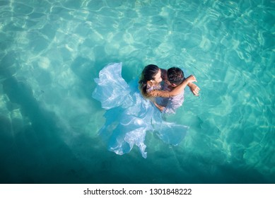 Young couple in a wedding dress stay and huging in a turquoise water.  Drone view. Honey moon concept. Romantic concept.  Trash the dress photosession. Holidays in a tropical country.