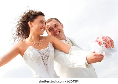 young couple in wedding wear with bouquet of roses.