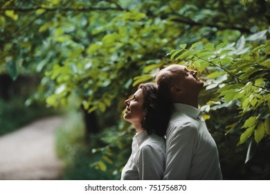 Young couple in white shirts stands under green summer trees