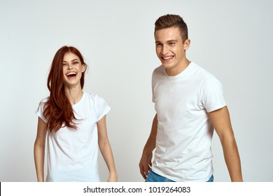 young couple in white t-shirts laughing on a light background