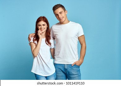 young couple in white t-shirts on a blue background