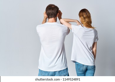 A young couple in white T-shirts is standing with his back to the camera.