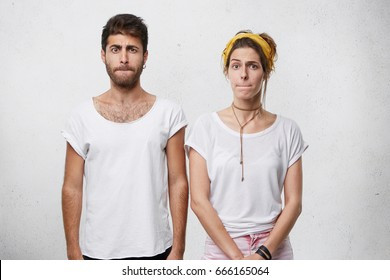 Young couple in white T-shirts standing close to each other pressing their lips with displeasure having bad mood after quarrel. Bearded male with stylish hairstyle standing near his pretty girlfriend