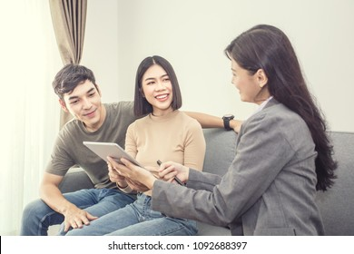 Young Couple Who are looking for Purchasing/ Renting New Home. Professional Real Estate Agent talking to Customer for Contracts. Vintage tone.