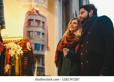 Young couple window shopping for Christmas gifts