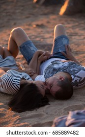 Young couple with wine having romantic date on sunset beach